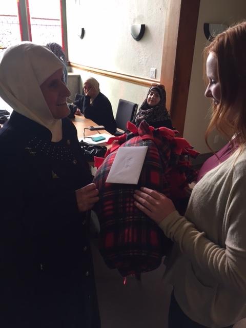Faith presents plaid cuddle blanket to Malaka Tonbakj.