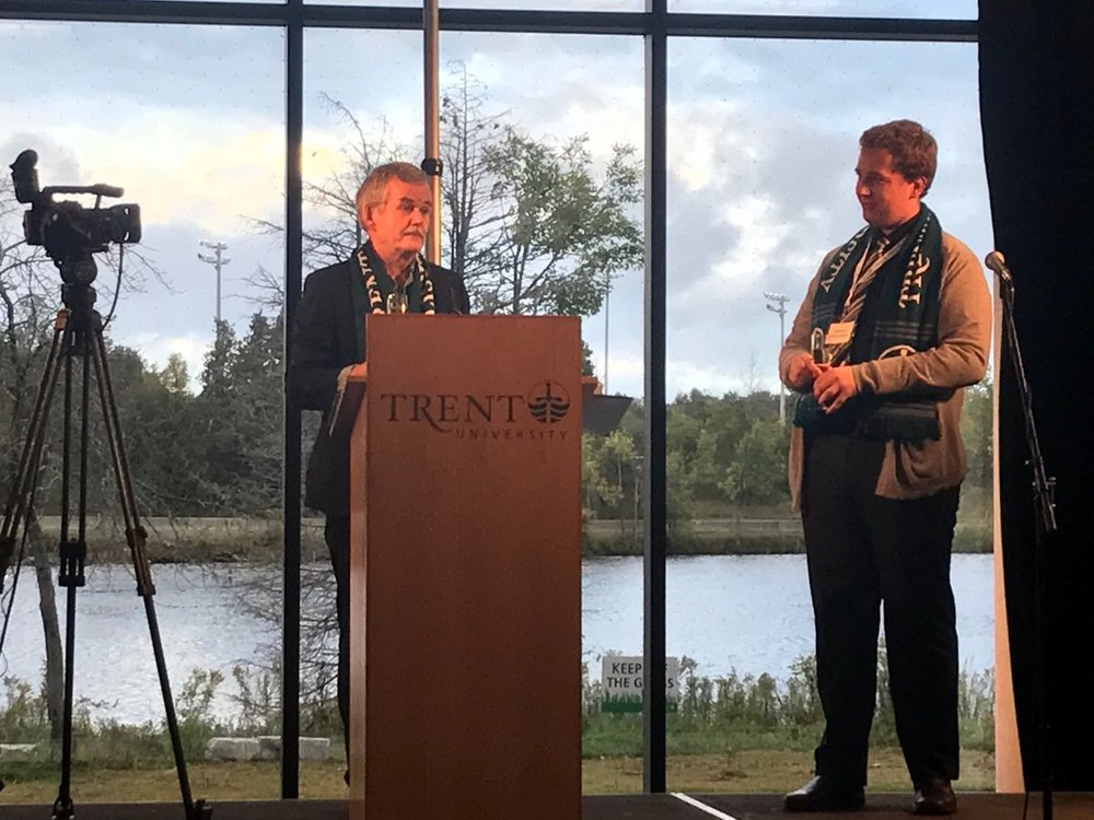 Trent University President Dr. Leo Groarke speaking at Trent Student Centre opening, with Otonabee River as backdrop (photo via Marilyn Burns, Trent University)