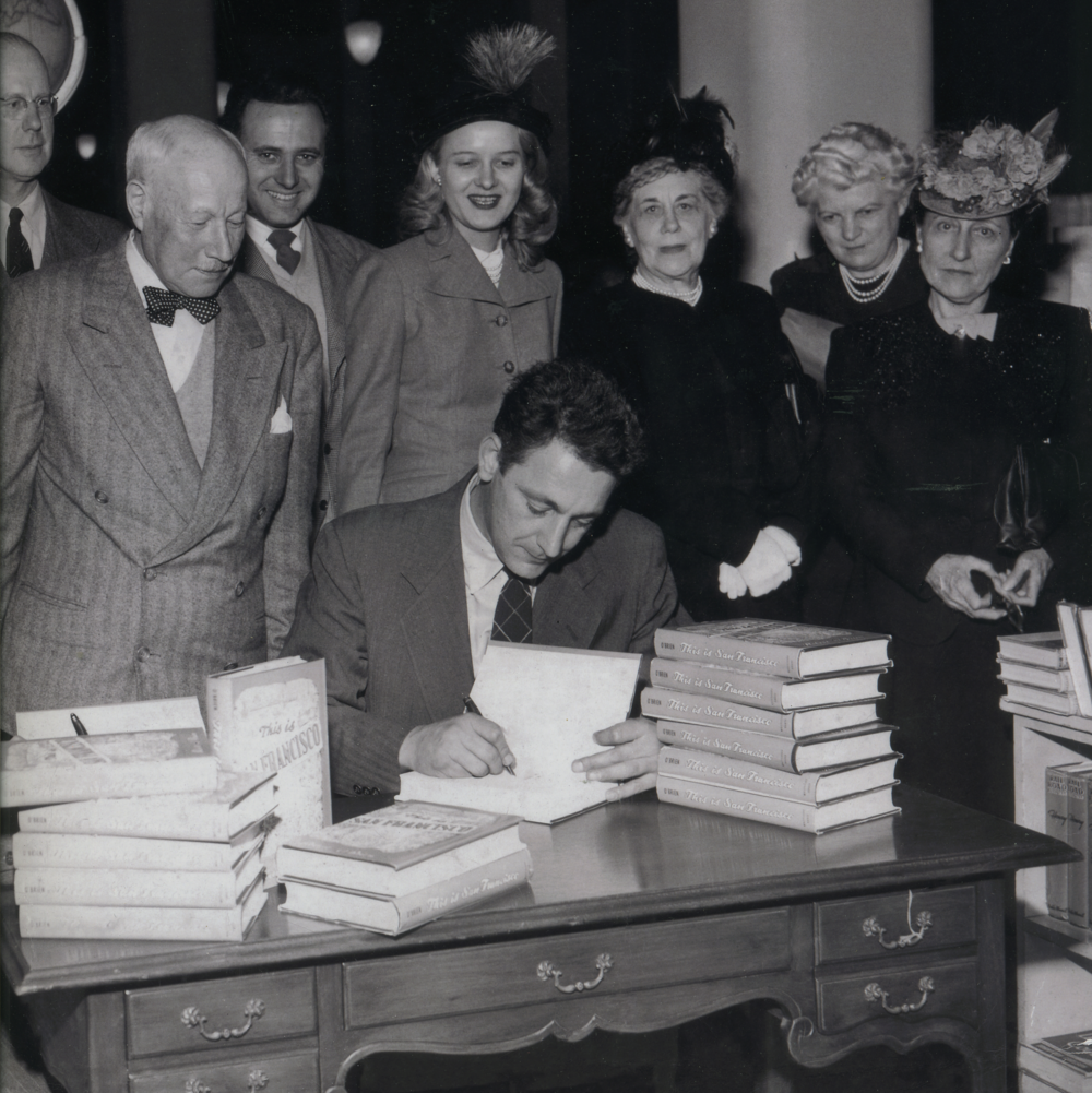 Robert O'Brien signing This Is San Francisco, in San Francisco, 1950.  The ladies LOVE feathers!
