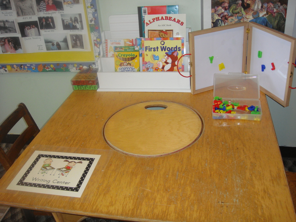 Our writing center includes books, magnet letters, a dry erase board, alphabet stamps, and LOTS of paper!