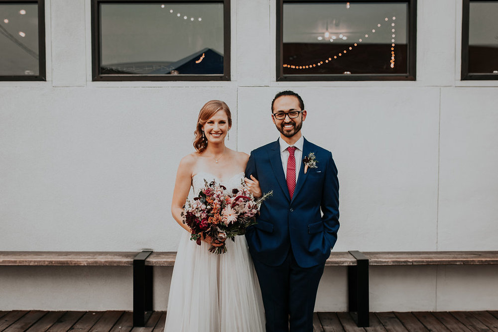 Couple at Union Pine with bright wedding flowers