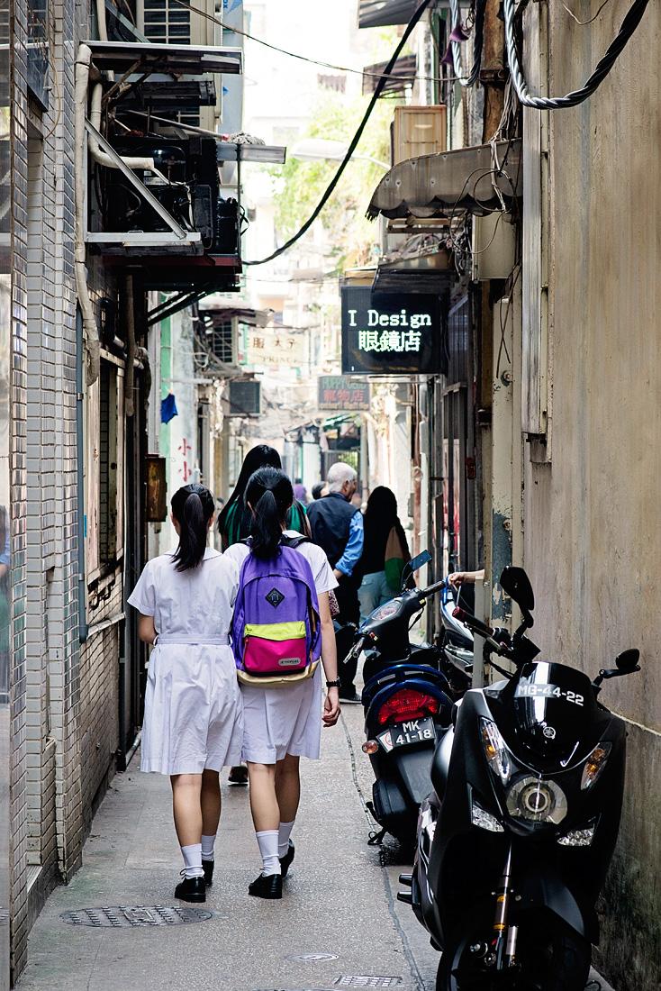 Schoolgirls walk down a laneway in Macau