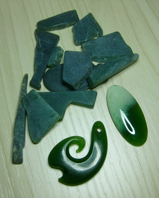 From the vault: a small pile of rough Greenstone that was given to me several years ago and my recently acquired pieces from the antique shop: a Matau and an oval cabochon.