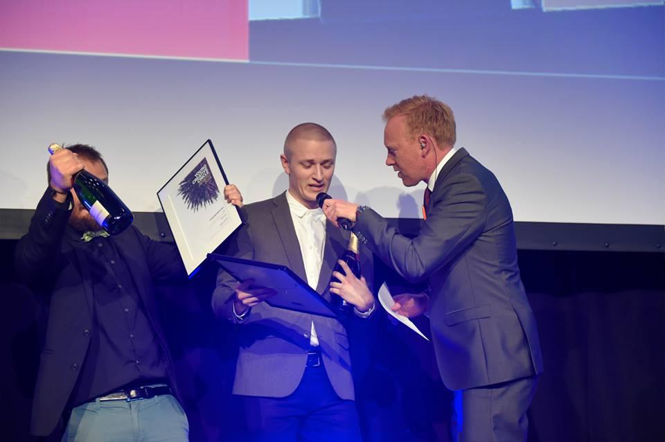 YCCA-vinder i Design, Julius Harrebek. Er her modvilligt ved at få stukket en mikrofon ind i munden af en målrettet Breinholdt (Julius ergrafisk juniordesigner hos Scandinavian Design Group, btw)