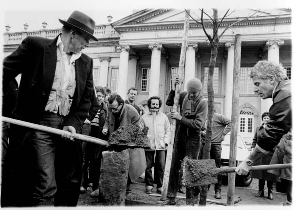 "Photograph of Beuys installing ""7000 Oaks"" at Documenta 7, 1982. Beuys had large basalt stones placed in an arrow pointing to a single oak tree that he had planted. Beuys declared that the stones could not be removed unless an oak tree was planted beside it  Source"