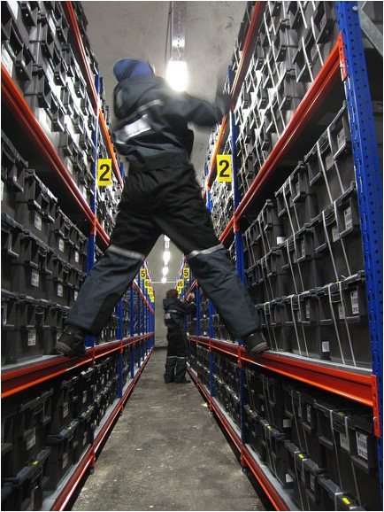 A worker straddles two rows of seeds in the vault near the North Pole