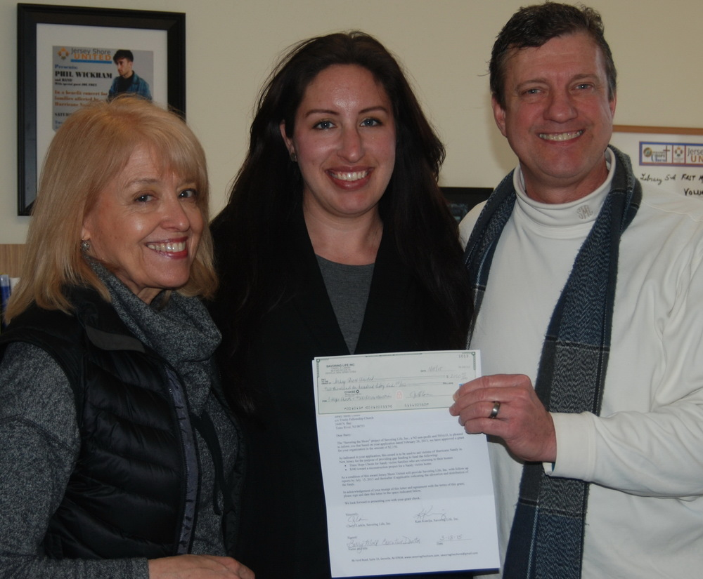 Cheryl Larkin (left) and Kate Kurelja present a Savoring grant to Barry Moll of Jersey Shore United.