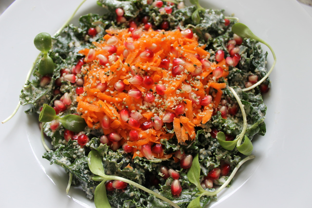 "Kale Salad With Sunflower Sprouts Carrots and Pomegranates What a way to start a food blog with one of our family's  favourite salads. Yes,  even my 15-year old love salads!  But this didn't happen overnight. You see, my boy grew up not watching cartoons but the sports networks and The Food Channel.  So you can just imagine cooking for your child whose idea of a delicious meal being the celebrity chef's creations!  But like they say patience and perseverance always pay off. One meal at a time and my foodie is finally on my side. He's my greatest fan and hardline critic rolled into one.  I love it! My kitchen is always busy as he  doesn't just have the appetite but also his own ideas about great flavours or what is exciting and yummy -  which makes food preparation  even more interesting for me. So kale has been getting a lot of attention lately which is deserving for the king of greens. It could very well be the new beef!  It's packed with nutrients and is high in iron, Vitamins A, K, calcium and protein among other things.   Sunflower sprouts or micro greens are also powerhouses of nutrition. They are little  plants just breaking out from the seeds and are loaded with enzymes, Vitamins A, D, E and B complex and 3.5 oz. of these sprouts boasts 25 g. of proteins!  Adding carrots and pomegranates to this salad just make it a nutritious mix for our plates! Kale Salad With Sunflower Sprouts Carrots and Pomegranates Ingredients: 1 bunch curly kale de-stemmed, washed,  finely sliced and dried 2  medium size carrots peeled and grated 1 1/2 c. sunflower sprouts seeds of 1 pomegranate 1/4 c. Hemp seeds Creamy Sesame Dressing: 1/2 c.  unhulled sesame seeds 2 cloves  garlic 1/3 c. organic and unpasteurized apple cider vinegar 1 1/4 c. warm water 11/2  Tbsp. maple syrup 1/2 t. Himalayan salt 1 1/2  Tbsp. cold pressed extra virgin olive oil 1. To remove the seeds of the pomegranate, cut it in half then get a bowl and fill it with water. Submerge them into the water  then pry out the seeds from the rind with your fingers.  Remove the white pith as much as you can. The seeds will sink to the bottom of the bowl while the white pith will float. 2. Place all the ingredients for the dressing into a blender,  a magic bullet or Nutribullet and blend until smooth. Add a little more water if you find it too thick.  With your hands, ""massage"" the dressing into your kale 'til it gets soft and nicely coated. Taste the kale and adjust accordingly… it may need more sweetness, tanginess or salt.  Let it sit for 15 mins. in order for the dressing to be absorbed. 3. Just before serving, add the carrots, sprouts, pomegranate seeds and sprinkle the hemp hearts. When serving the salad to guests, put the toppings on each plate…it's great for them to see and enjoy the vibrant colours of the dish!"