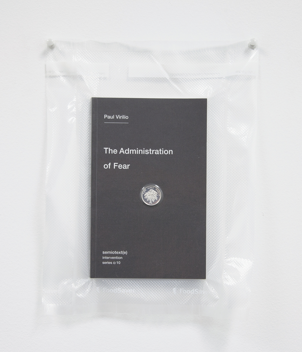 Brad Troemel    TSA No Fly List Vacuum Sealed Paul Virilio     -'The Administration of Fear' with AOCS Solid Silver Prosperity Treet coin  , 2013   10 x 8 inches