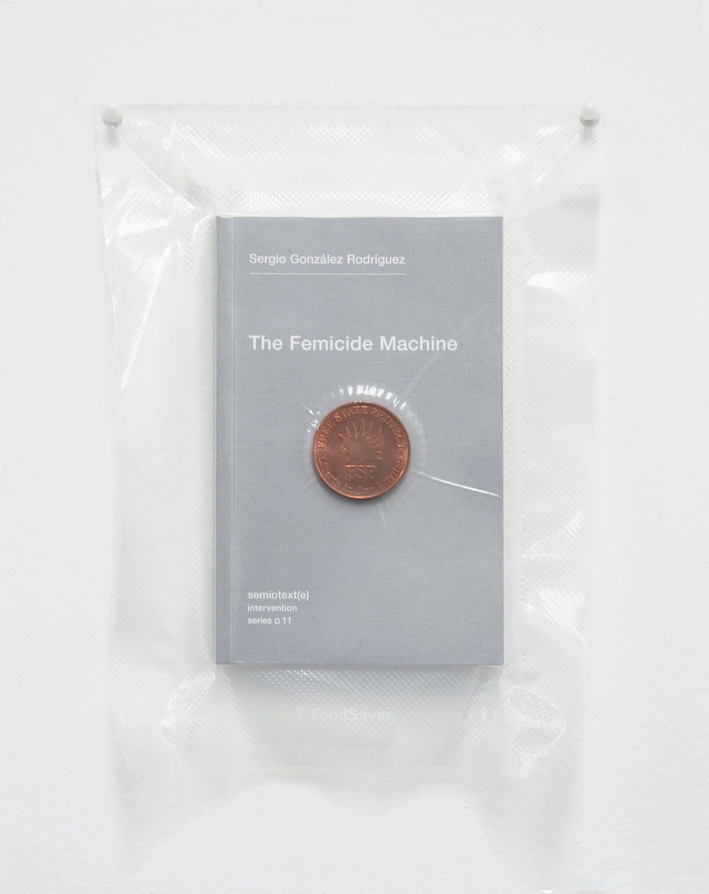 Brad Troemel   TSA No Fly List Vacuum Sealed Sergio Gonzalez Rodriguez -'The Femicide Machine' with AOCS Solid Copper Free State Project Porcupine Coin.   2013   10 x 8 inches