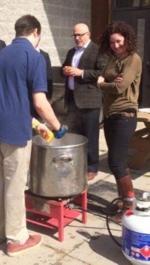 DEPUTY MINISTER ALEX BEZZINA AND CLINICAL DIRECTOR VICTORIA CREIGHTON SAMPLE STUDENTS' MAPLE SYRUP IN PROGRESS