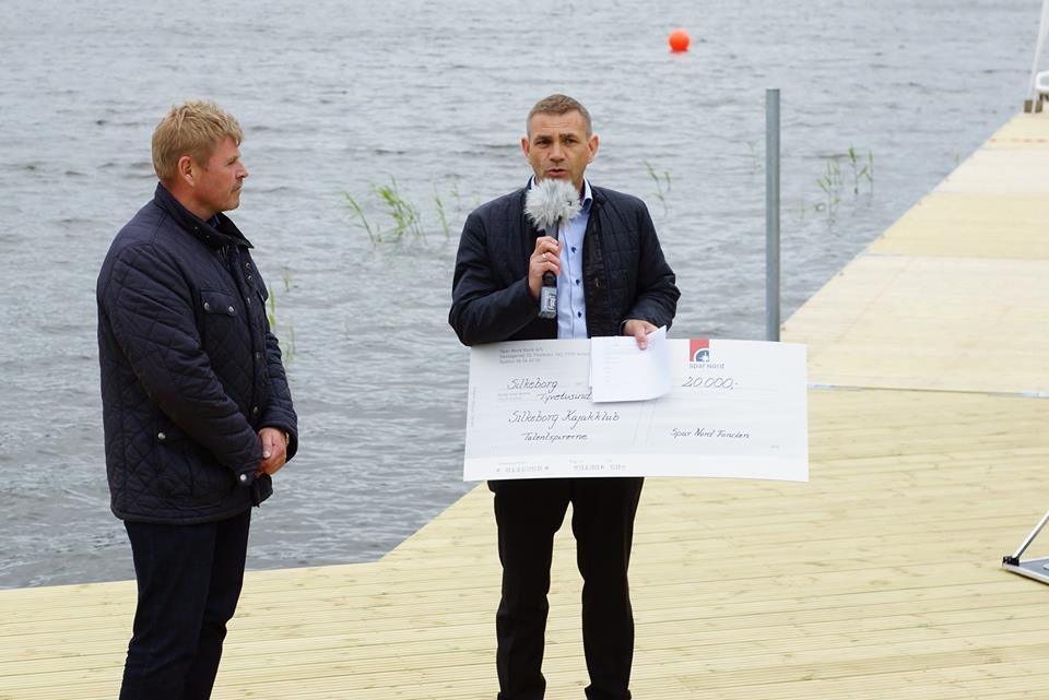 Kristen Søndergaard modtager check fra Spar Nord Banks afd. direktør Steen Rasmussen.