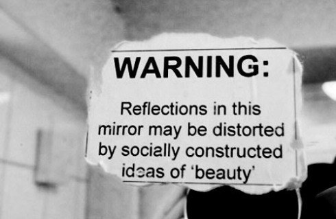"[feature image shows sticker on mirror that says: Warning: Reflections in this mirror may be distorted by socially constructed ideas of 'beauty'"" via]"