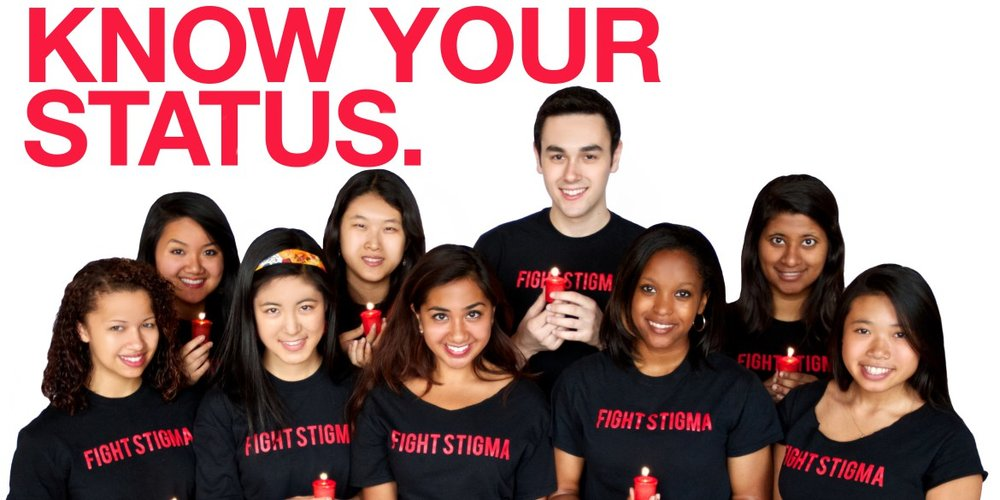 "[feature image shows 9 people holding candles and wearing t-shirts that say: ""Get Tested. Know Your Status."" via]"