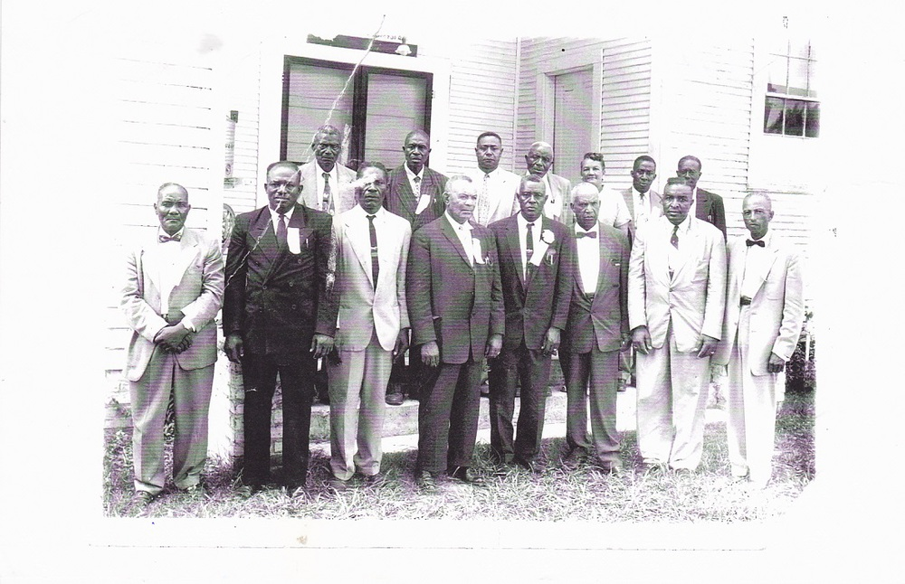 "Pastors, Officers, & Ministers of the East Carroll Baptist Association, late 1950s standing in front of North Star Baptist Church, pastored by my father & main character in Witness to the Truth.""  Back Row, left to right: Rev. Newson, Percy Knighten, Rev. Francis J. Atlas, Rev. Handy Jackson, Genevieve Shorter (Treasurer and first female elected to hold this position in 1953), R. B. Stevenson, Rev. N. B. McCall. Front Row, left to right: Rev. Spencer Hall, Rev. Freddie Green, Rev. J. H. Moore, Rev. Mansel Mason, Rev. O. L. Virgil, Rev. H. T. James, Rev. Percy H. Henderson, Rev. John H. Scott (President)"
