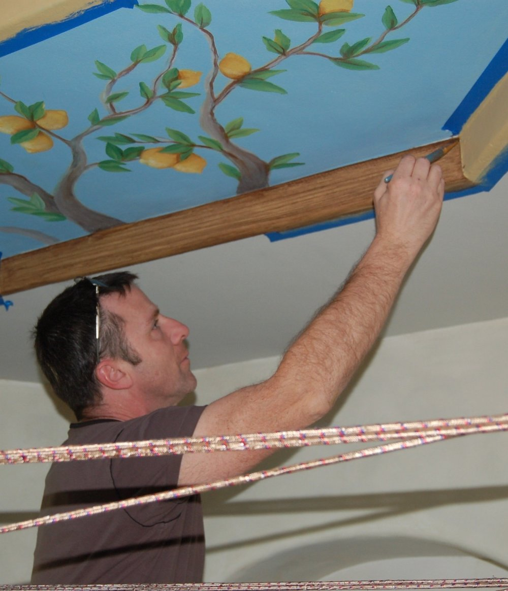 The ceiling mural was painted on site-the soffit drops were faux wood grained to add structure and frame the mural.