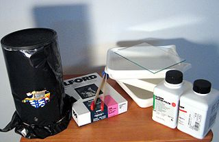 A home-made pinhole camera (on the left), wrapped in black plastic to prevent light leaks, and related developing supplies. Courtesy  Douglas Whitaker  via Wikipedia