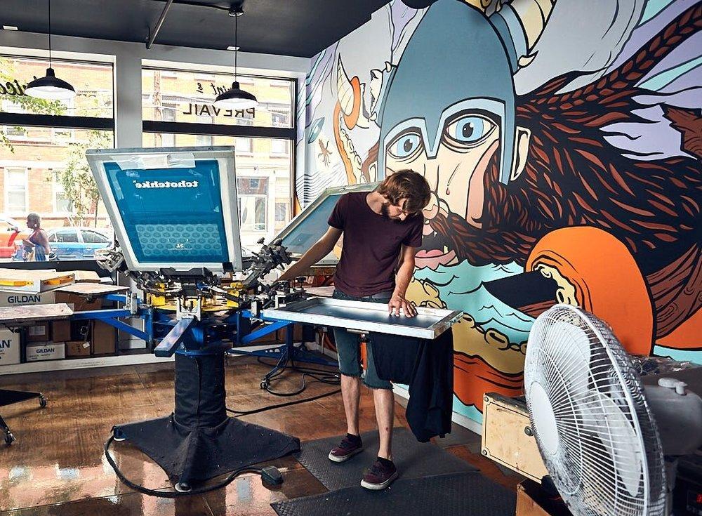 Matt Dorman, WHBV's Lead Print, works on t-shirt printing in the print studio.