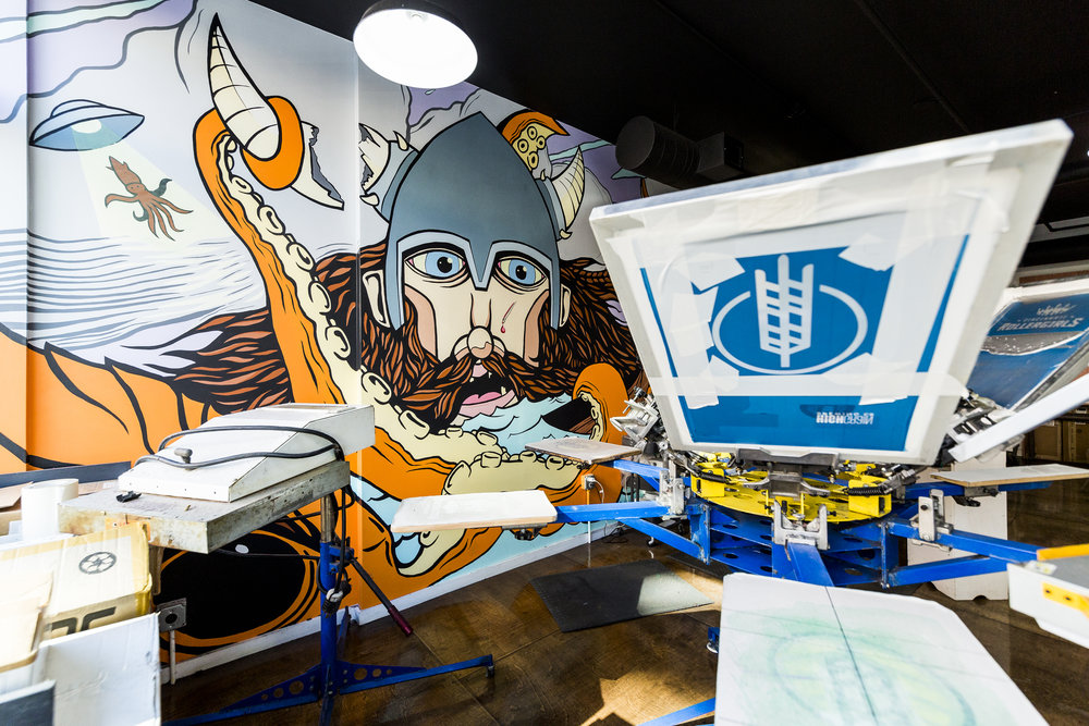 Silkscreen tee shirt press room with viking, octopus, alien mural by Matt Dorman
