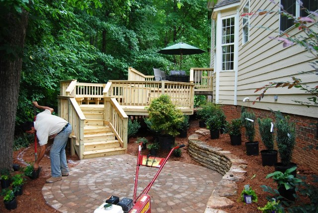 This very small area has a multi-level deck, stone patio, and a planted retaining wall. (click to enlarge)