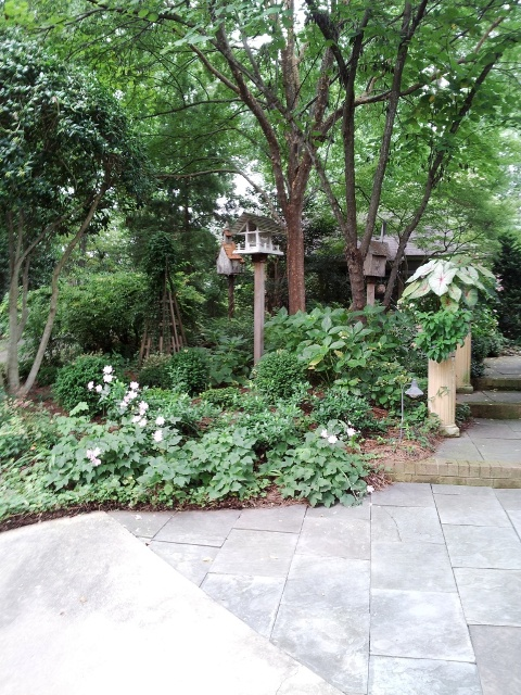 A collection of fun birdhouses, a pyramid trellis, planters elevated on elegant  columns, layered plantings, hardscaping and elevation changes all add interest in this well designed small space. (click to enlarge)