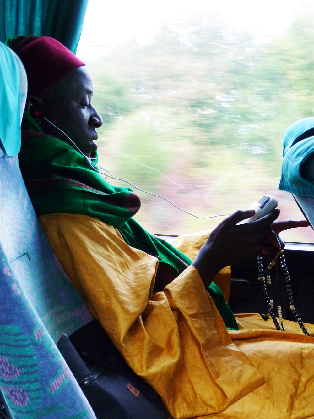 In a tour bus, Imam Sy, a leader of the Senegalese Tijāniyyah, is listening to the recording of his concert the day before.   Oct. 2010