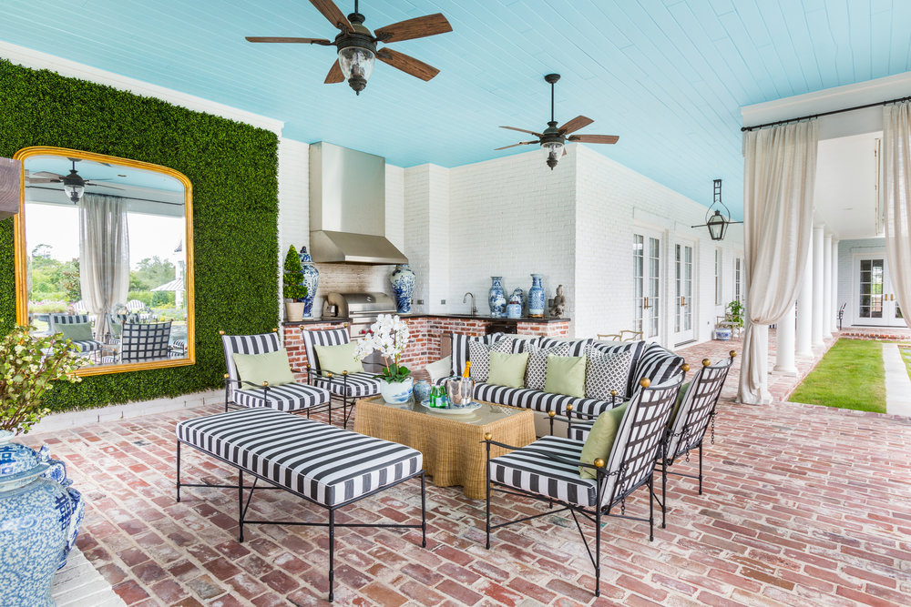 Outdoor living room with black and white stripes, blue ceiling, faux boxwood wall, designed by Jamie House Design