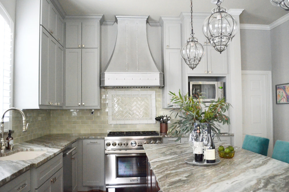 Sugarland Texas kitchen remodel by Jamie House Design. Grey kitchen cabinets, marble counters, and custom range hood.