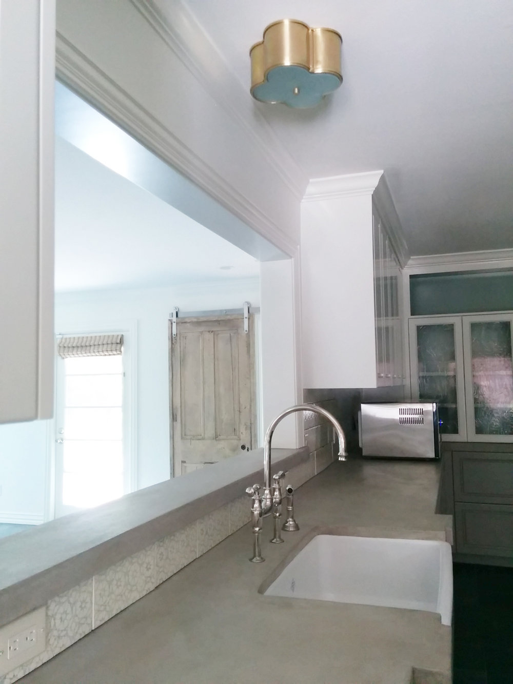 Farmhouse sink with concrete counters. Visual Comfort flushmount.