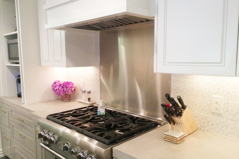 Pratt and Larson tile backsplash with stainless steel panel behind range in Houston kitchen remodel by Jamie House Design.
