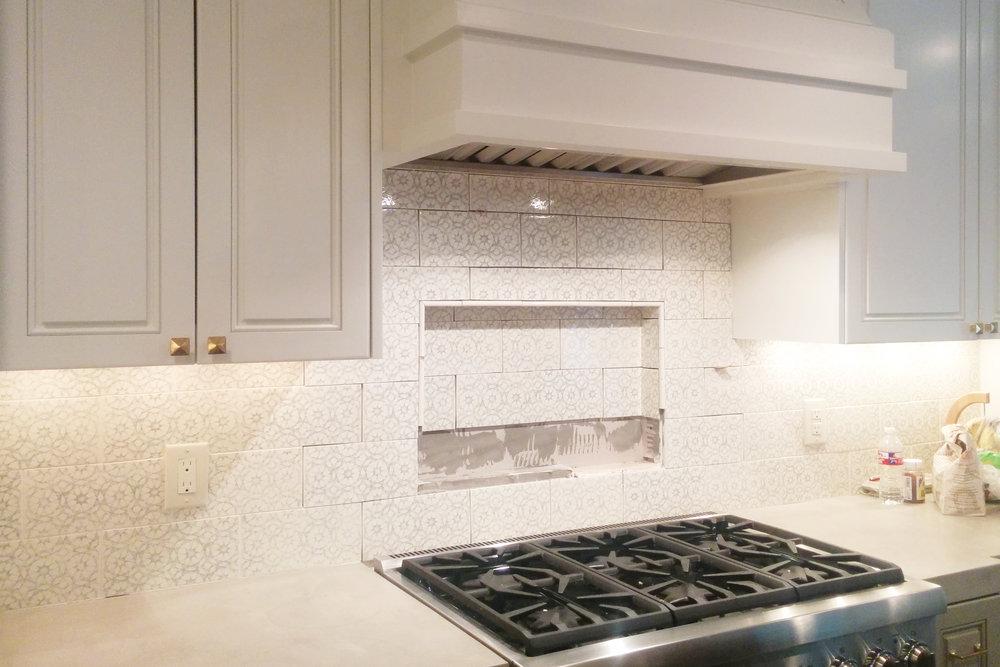 Installing niche behind range in Houston kitchen remodel by Jamie House Design. Pratt and Larson tiles.