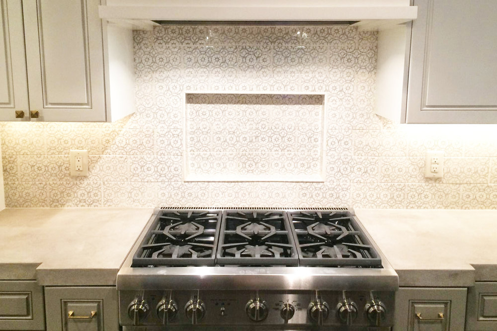 Pratt and Larson tiles on backsplash behind range in Houston Texas kitchen remodel by Jamie House Design. Concrete counters in kitchen.