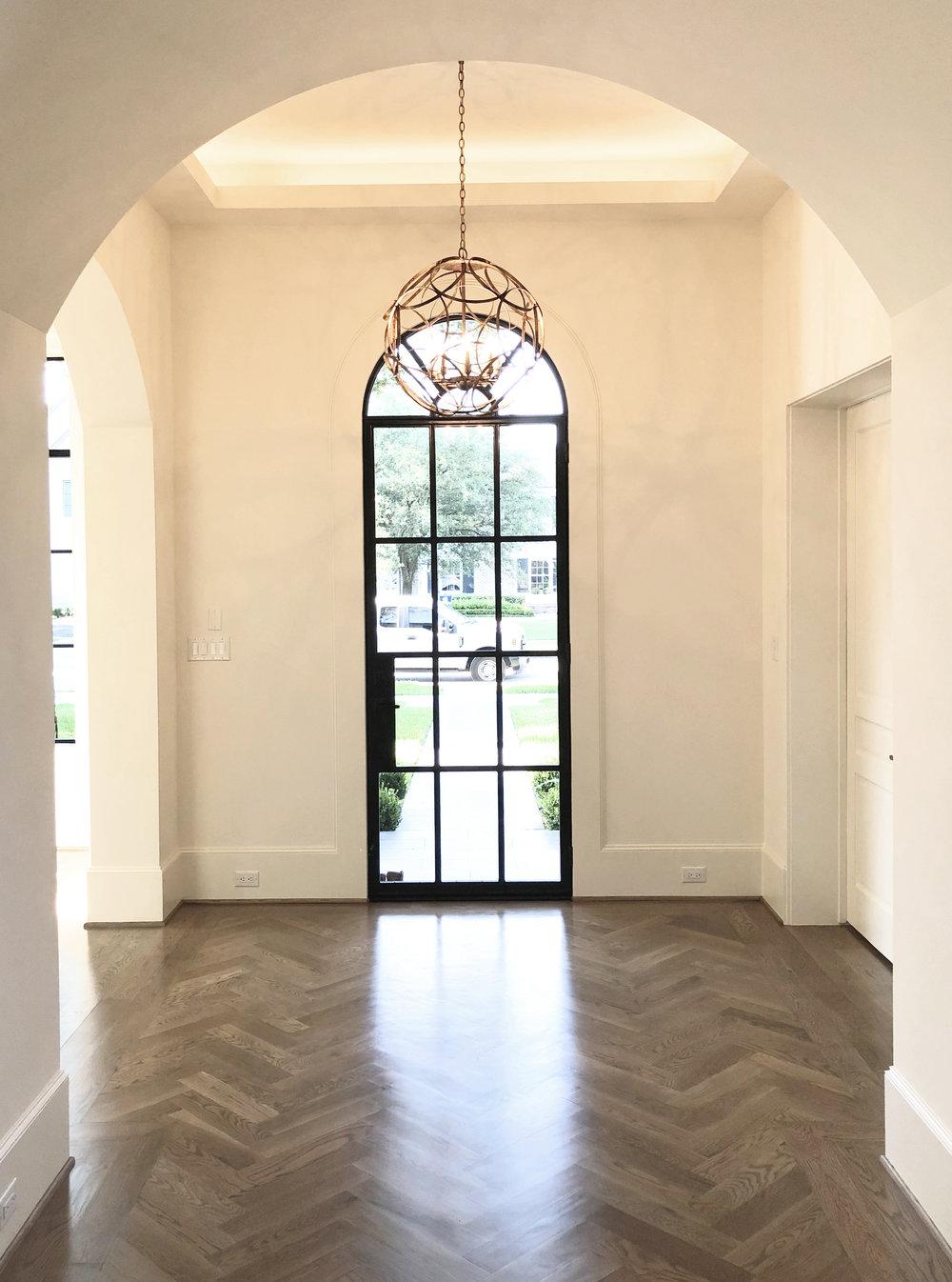 Modern entryway designed by Jamie House Design with herringbone wood floors
