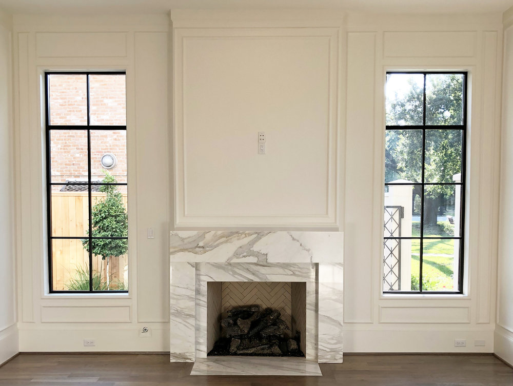 Custom designed marble fireplace with steel windows in River Oaks home designed by Berlin based interior design firm Jamie House Design