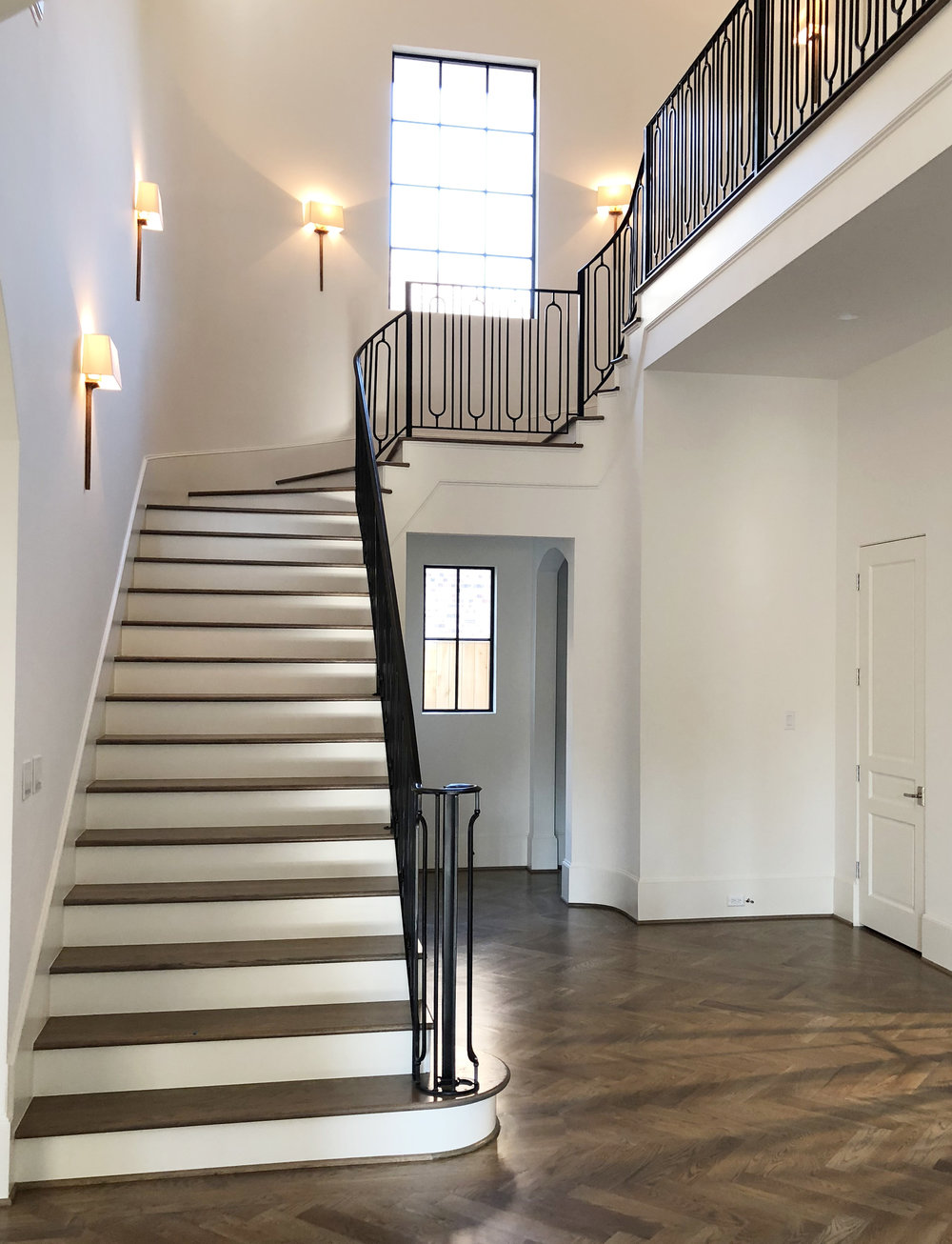 Stairwell with iron railing and herringbone wood floors in Houston's River Oaks neighborhood designed by Berlin based interior designer Jamie House, built by CM Batts Developers.