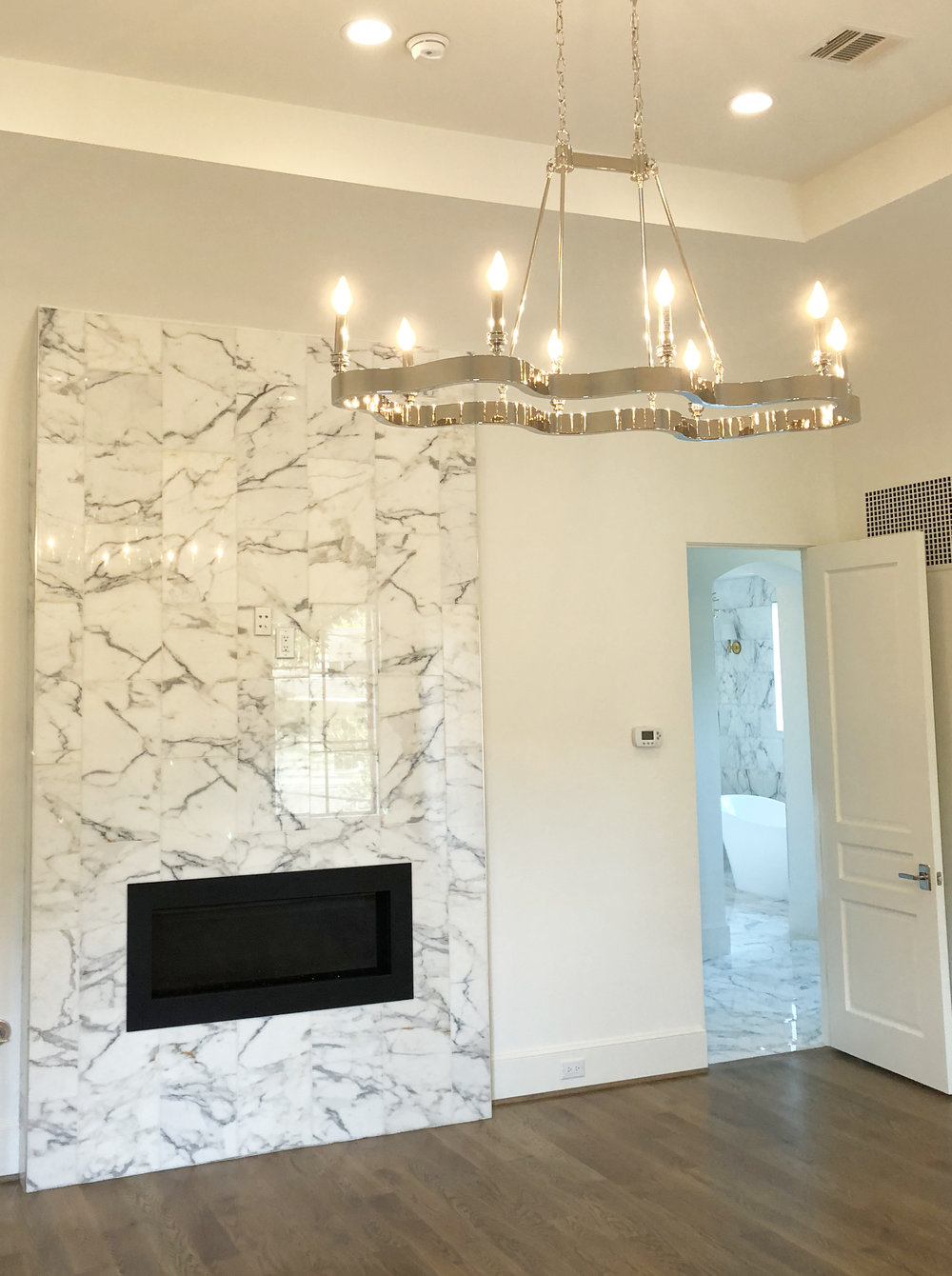 Custom contemporary marble fireplace with platinum chandelier in the master bedroom of a Houston River Oaks home designed by Berlin based interior designer Jamie House. Built by CM Batts Developers. Jamie House Design.