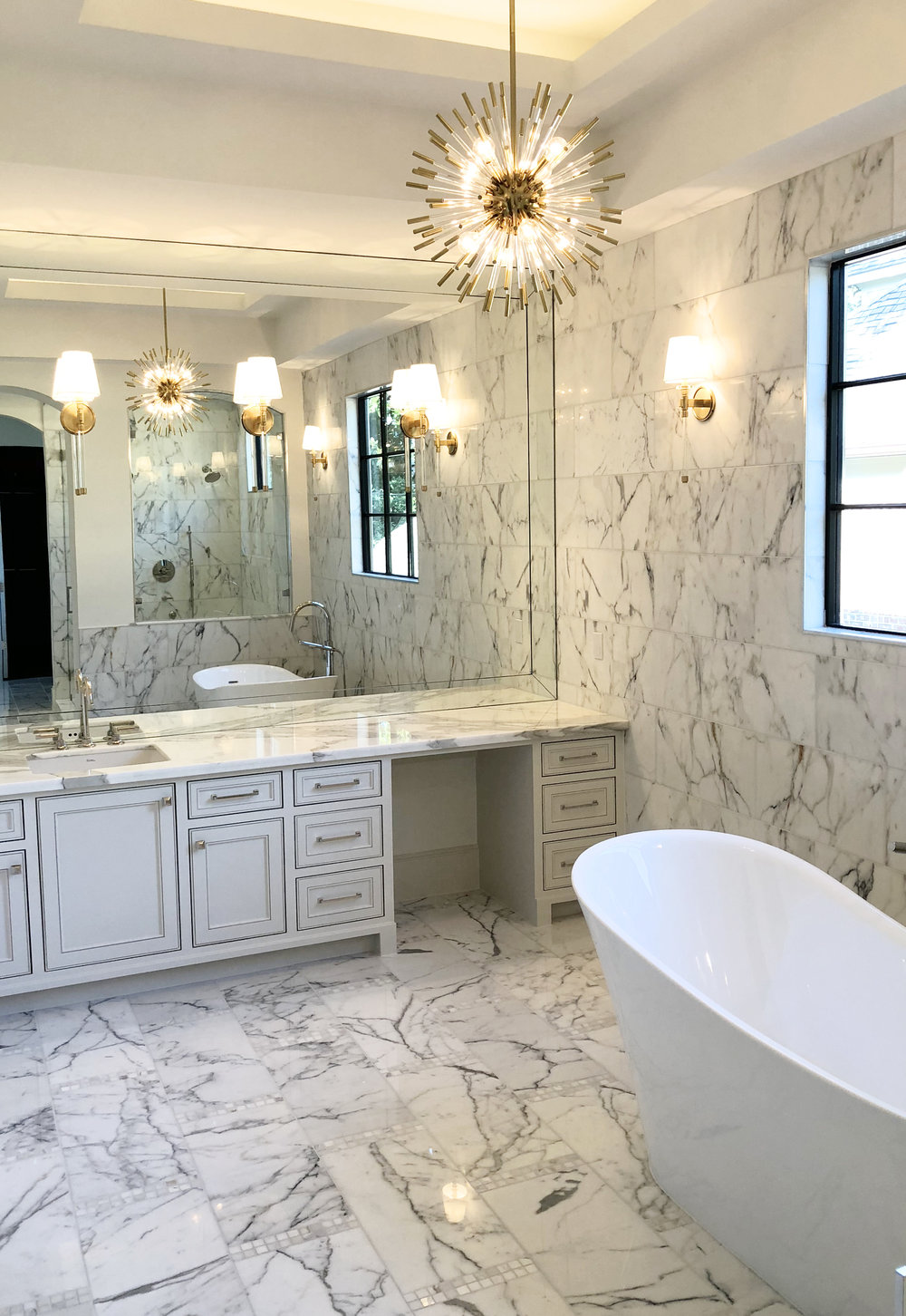 All marble white master bathroom with sputnik chandelier and freestanding bathtub designed by Berlin interior design firm Jamie House Design and built by CM Batts Developers.
