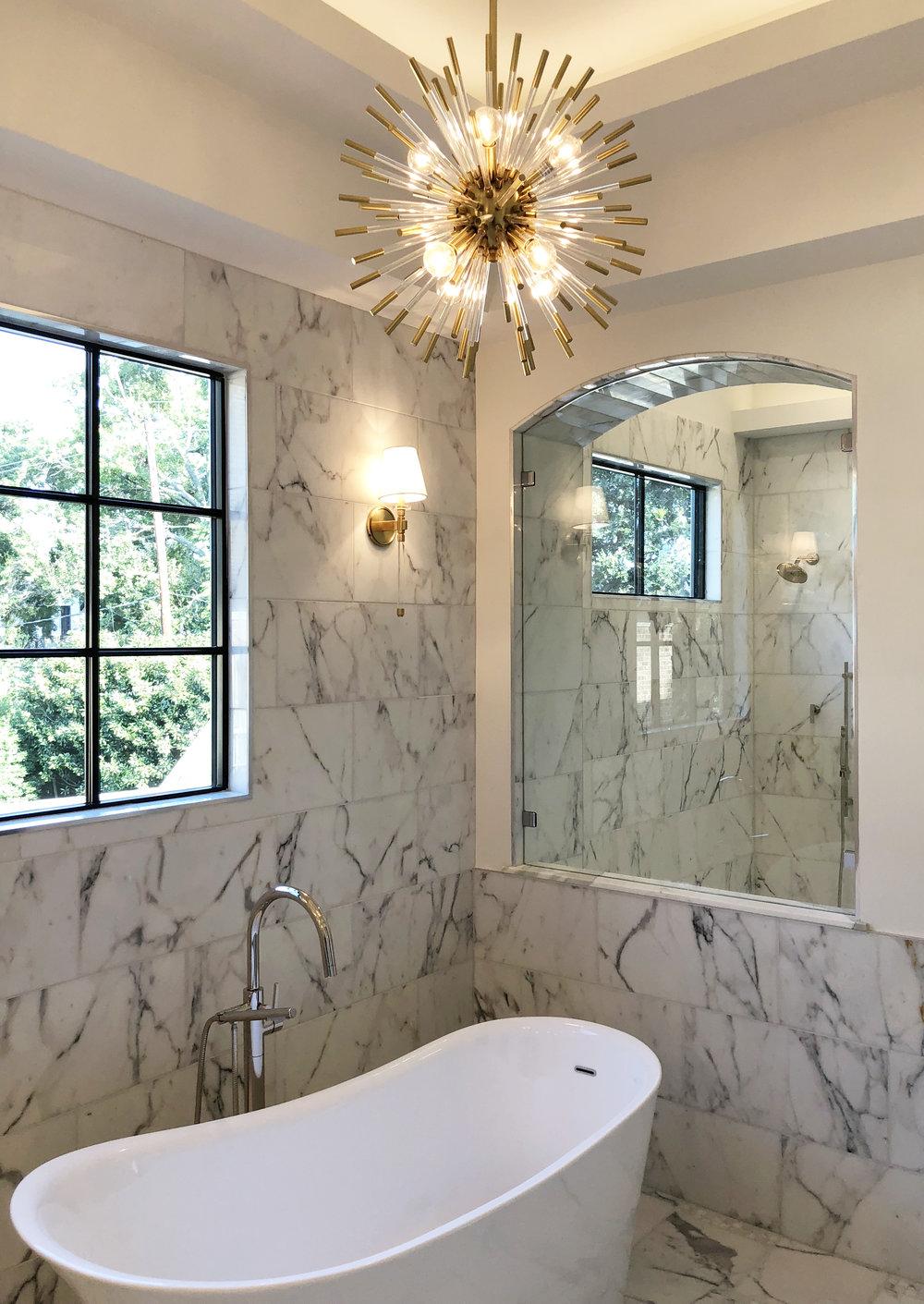Freestanding bathtub with Sputnik chandelier in an all marble master bathroom designed by Berlin interior designer Jamie House. Built by CM Batts Developers. Jamie House Design