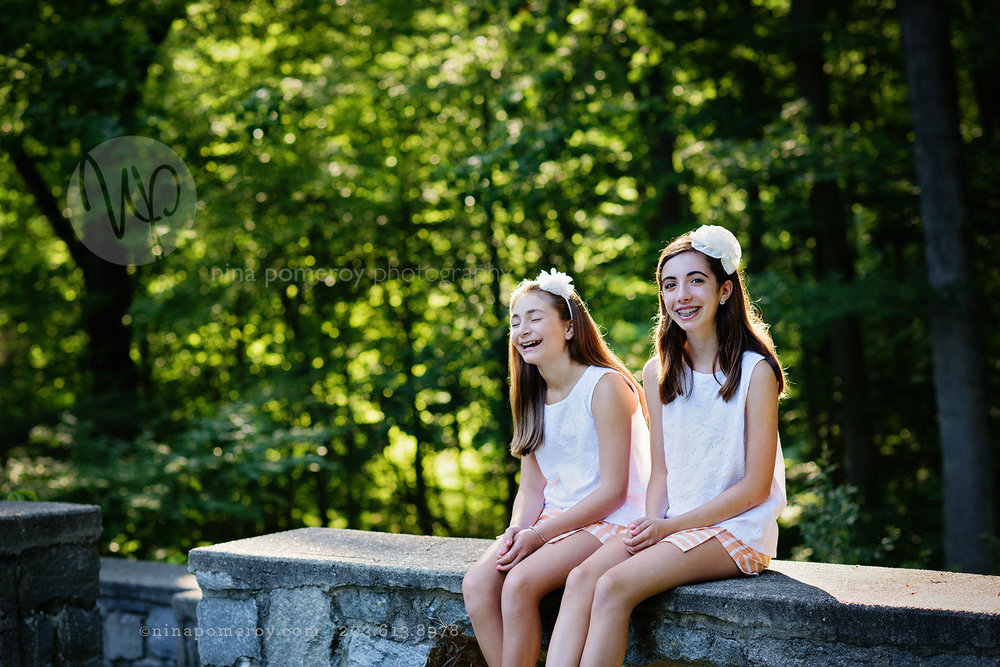 Laughing sisters sitting outdoors at a park for their annual portrait with Danville Photographer Nina Pomeroy.