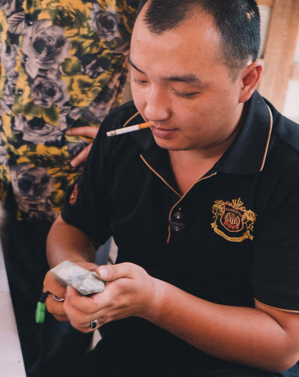 A mainland Chinese buyer assesses a piece of rough jade
