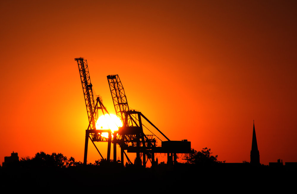Sunrise through the gantry cranes of the Red Hook Container terminal.  Photo courtesy of Bernie Ente