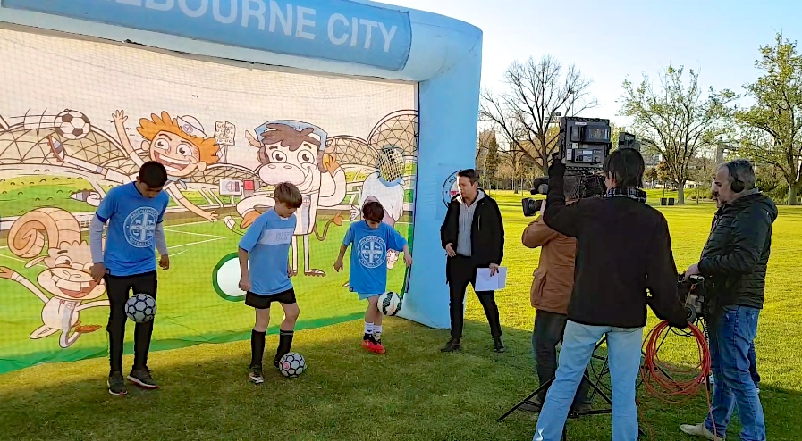 Collingwood City FC kids demonstrate soccer skills to weather presenter, Stevie Jacobs, during a live weather cross for Channel 9's Today Show.