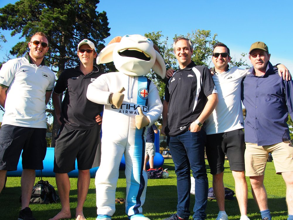 Coaches and staff from Collingwood City catch up with a Melbourne City mascot
