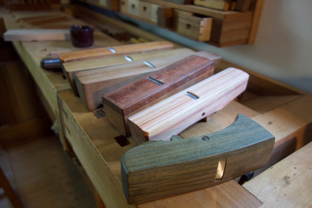 a few of my curved bottom planes, one third from front with applied sole is one of Jim's earlier planes