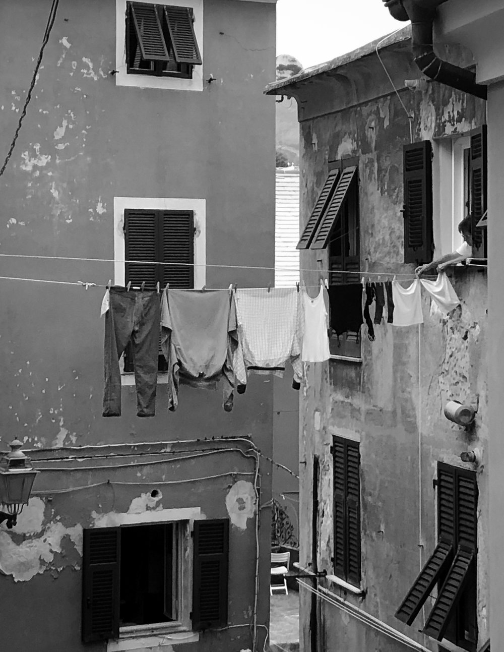The lady hangs clothes for drying stretching the rope from one building to another near the beach. Narrow streets to navigate. Classic scene.   #genova   #historic   #italy   #europe  #photography   #monochrome  #blackandwhite   #iphone   #canon   #adobe  #fashion   #vogue   #streets   #building  #architecture