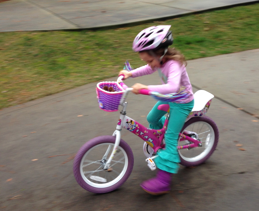 Guess who can ride her bike without the training wheels?
