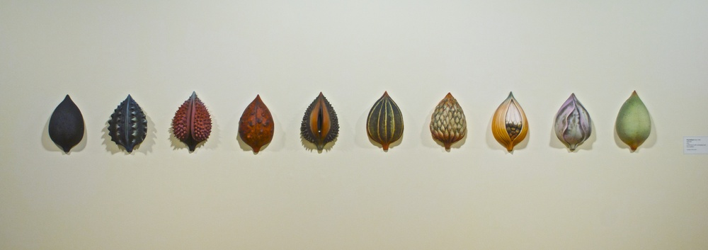"""10 Half-Pods"", a wall installation by Alice Ballard,  approximately 10 feet across and at a height of approximately 4.5 feet.  Each Half-Pod is made of earthenware with oxides, and colored terra sigillata"