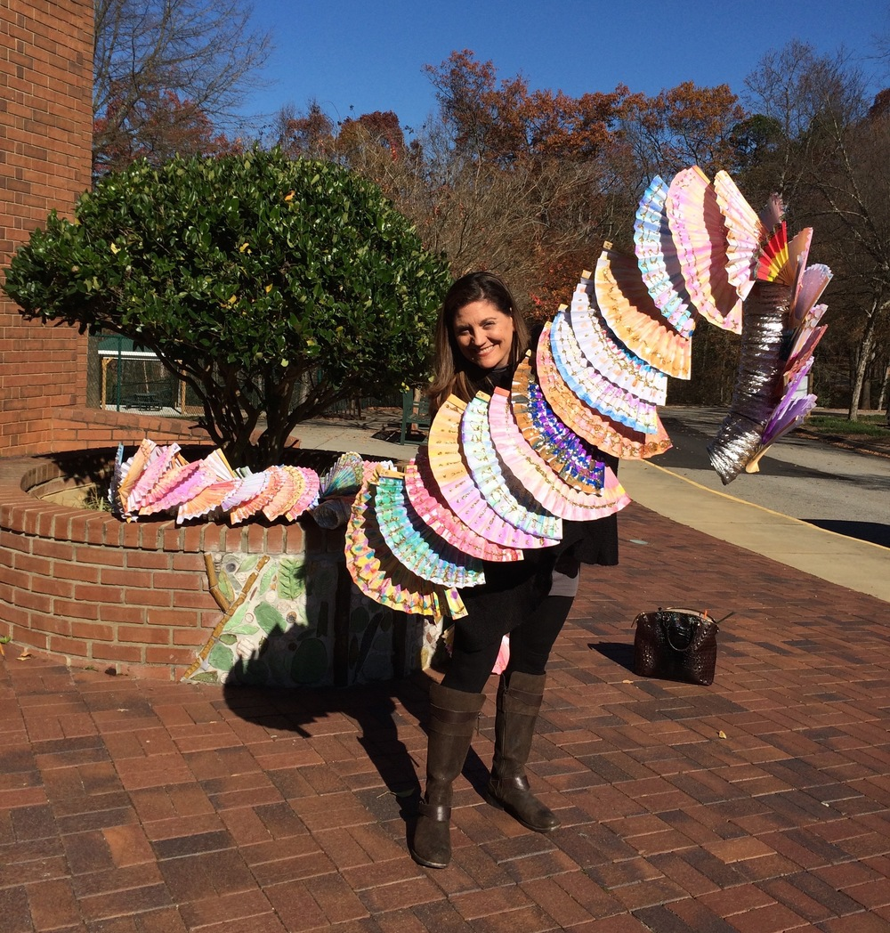 Allison Spinks holding a section of a dragon that consists of hand painted fans over flexible dryer pipe.