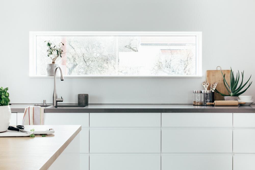 Kjøkkendesignet er en blanding av naturlige elementer som det lyse treverket på kjøkkenøya og den røffe Silestonebenkeplaten.