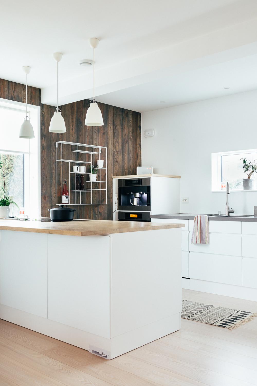 Det hvite kjøkkenet står i fin kontrast til den mør  ke drivvedveggen.